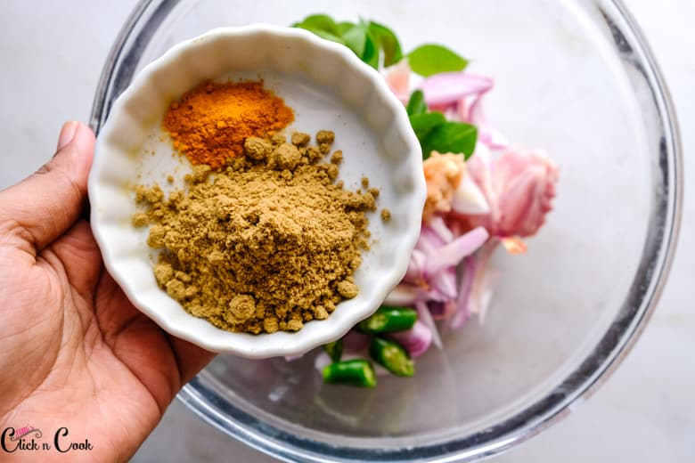 a bowl of coriander powder and turmeric powder is being added ti chicken in glass bowl