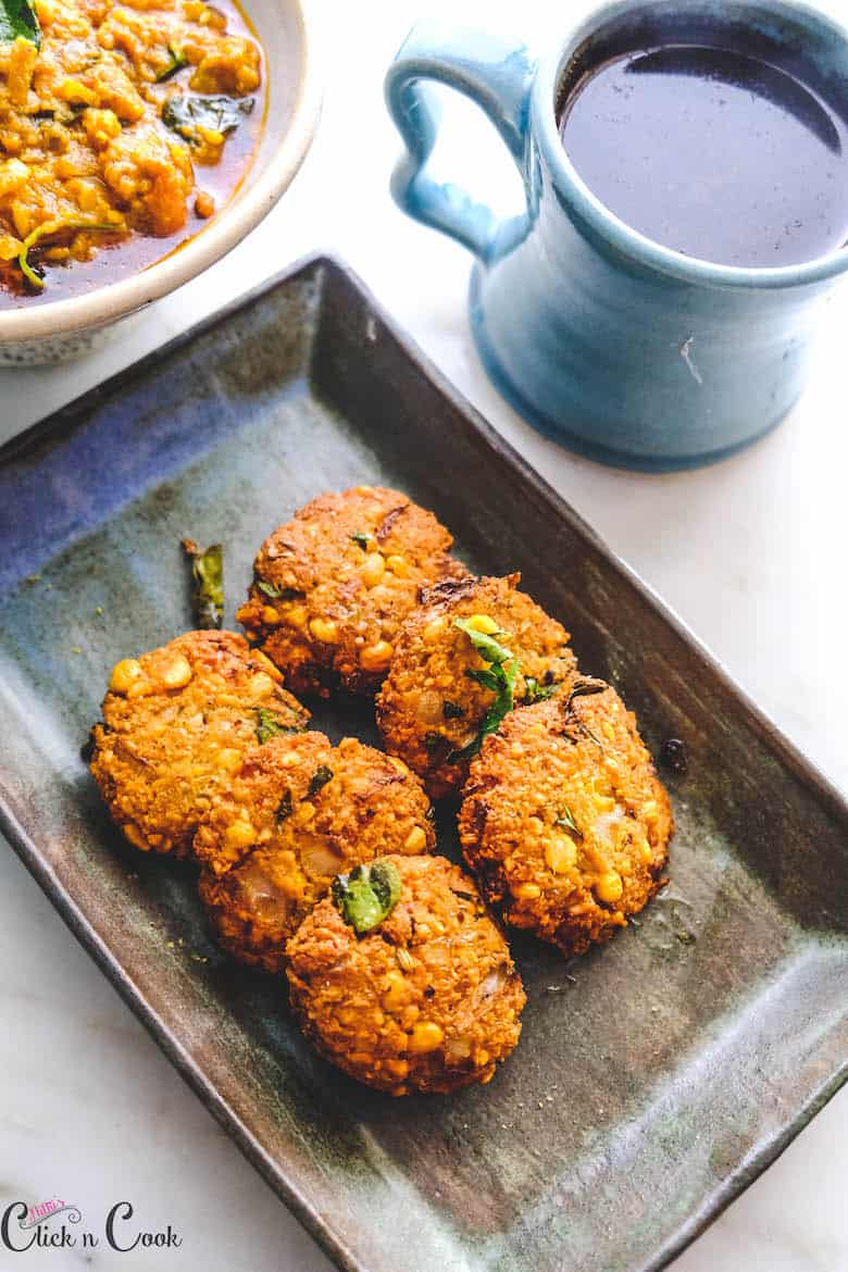 masala vada / paruppu vada is served in plate with mug of coffee aside