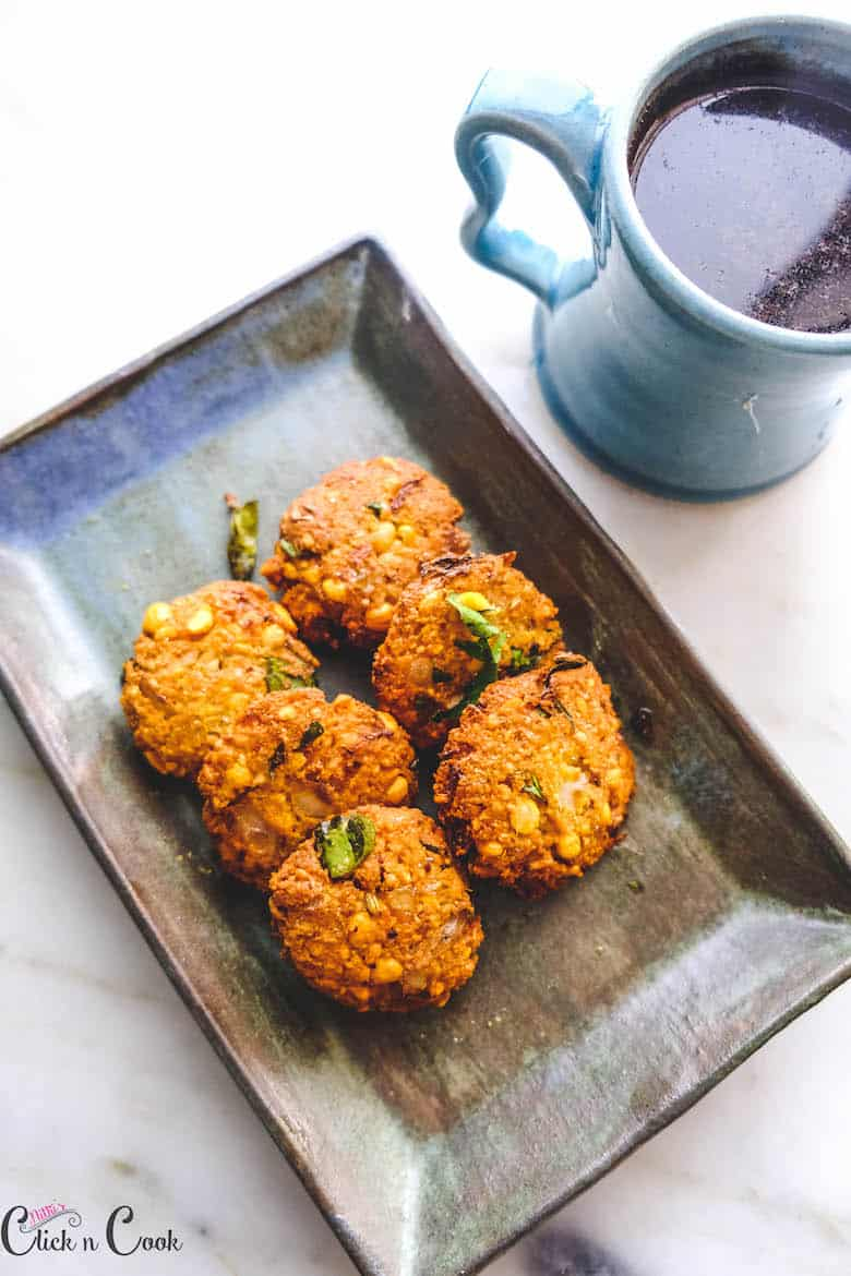masala vada is served in plate with mug of coffee aside