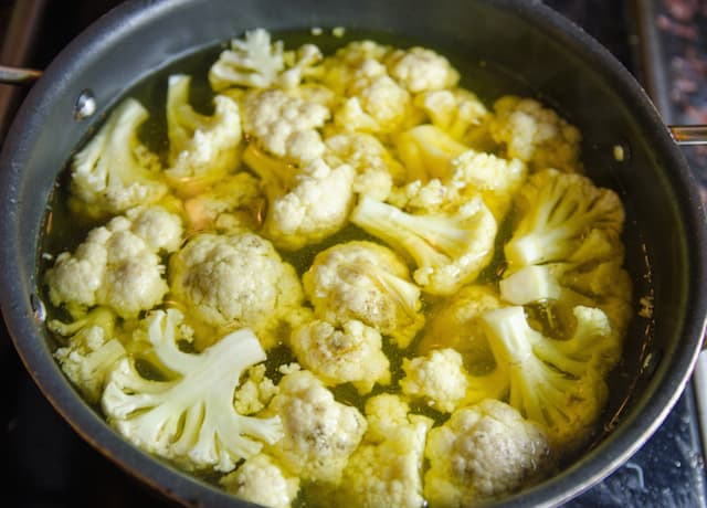 cauliflower is being added to water in deep pot