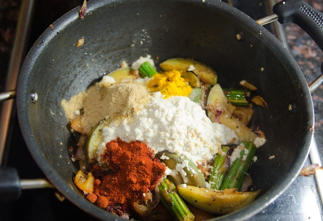 spices and ground coconut are being added to vegetables in deep frying pan