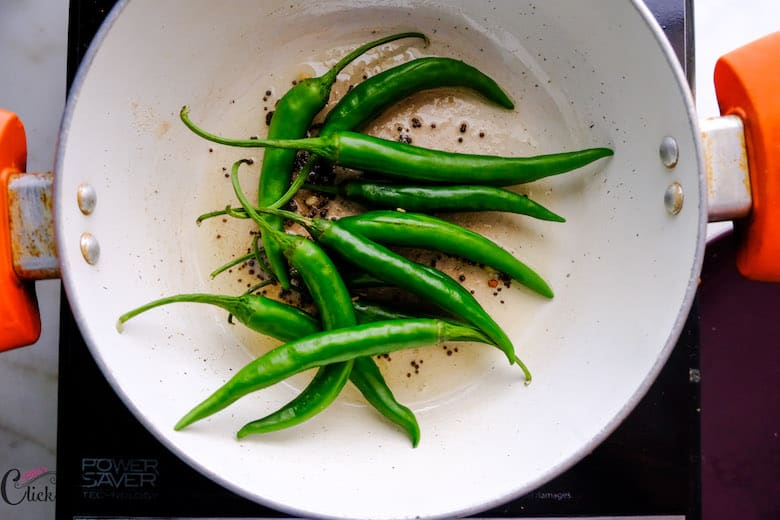 green chillies are being added to deep pot