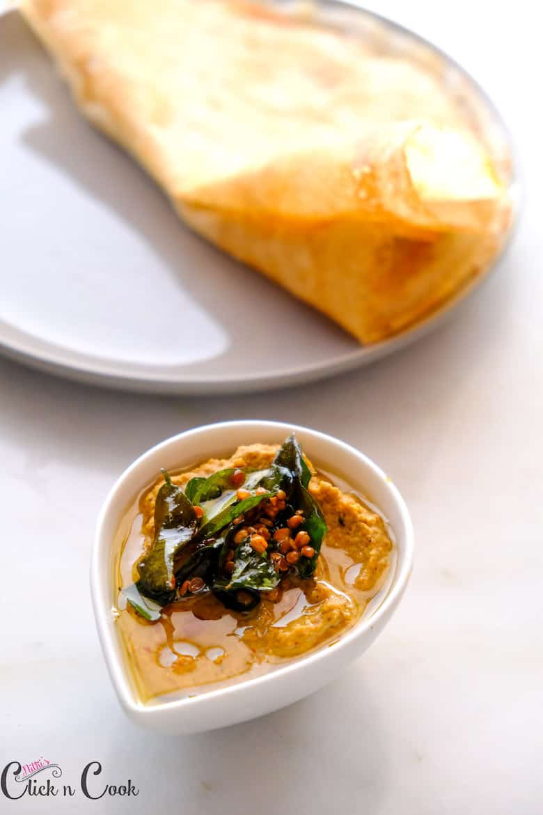 penaut chutney seasoned with curryleaves served in small bowl with dosa aside