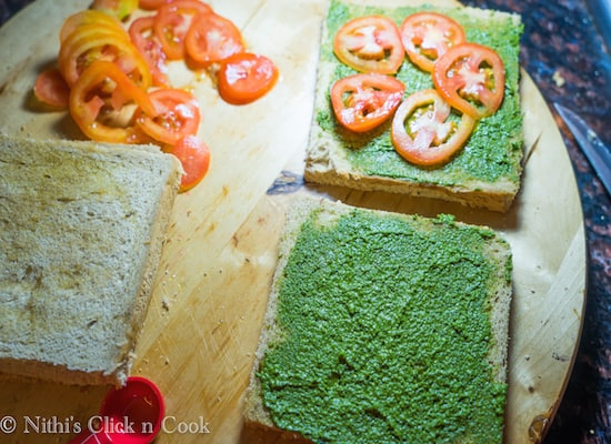 Apply some pesto sauce on onesie of the other bread and keep the sliced tomatoes on top.