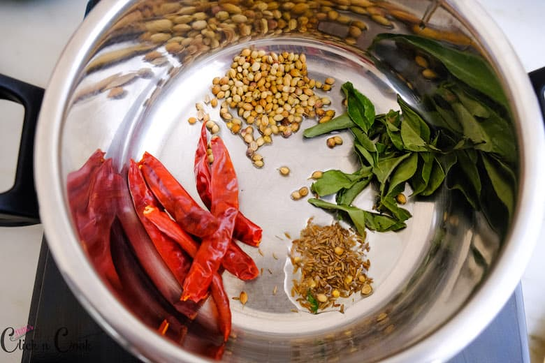 In a pressure cooker, cumin seeds, coriender seeds, curryleaves and dry redchillies are added