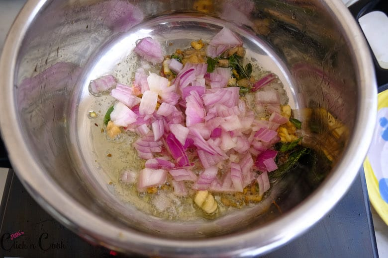 chopped onions are added to oil in deep saute pan