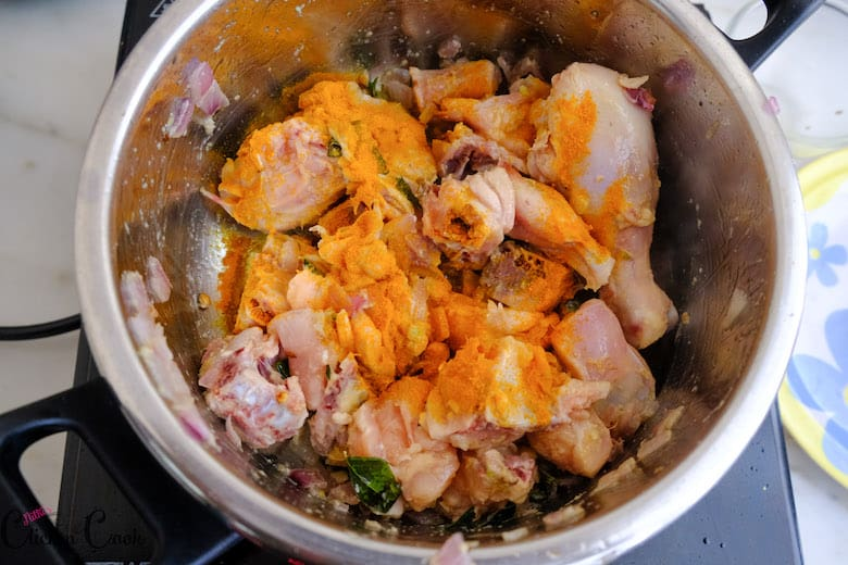 turmeric powder is added to chicken that has been sauted in deep saute pan