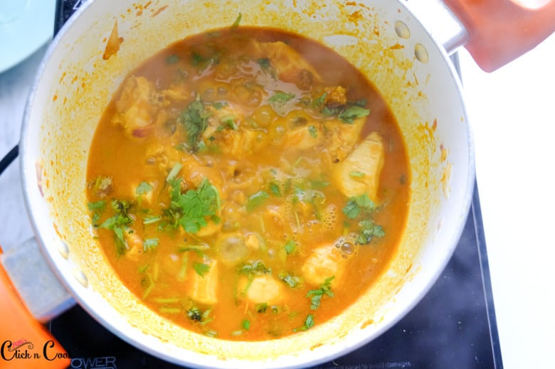 chicken curry recipe is being cooked in sauce pan