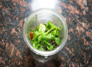 Take your blender, add coriander leaves, pepper, garlic and chillies and grind theminto a fine paste.