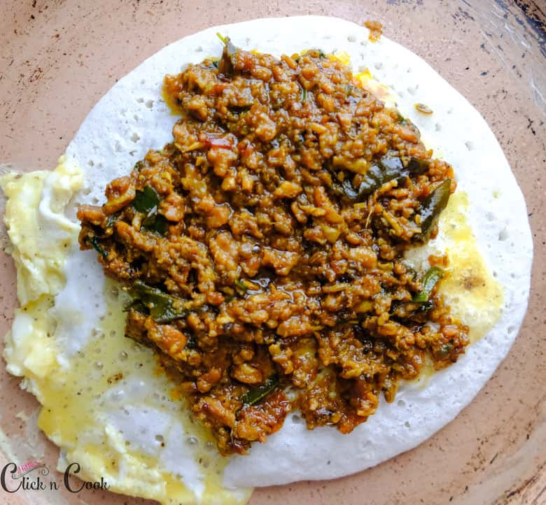 cooked mutton is spreaded over the dosa