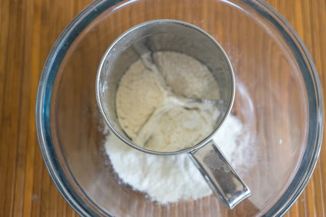 All purpose flour is being sifted in a wide glass mixing bowl