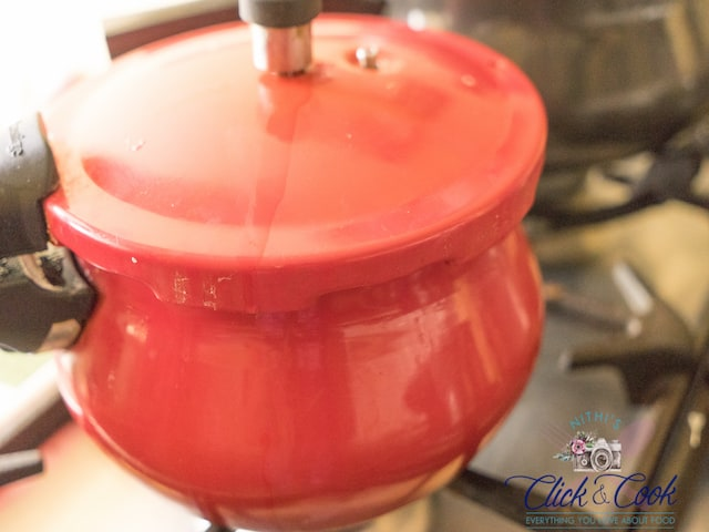 Red pressure cooker with whistle on is placed on the stovetop