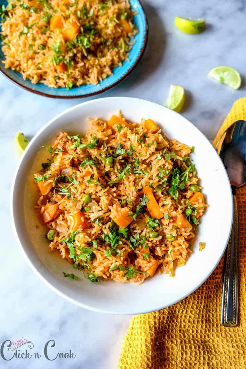 Mexican rice made with carrot and peas garnished with coriender leaves placed in a serving bowl with spoon aside and lemon wedges
