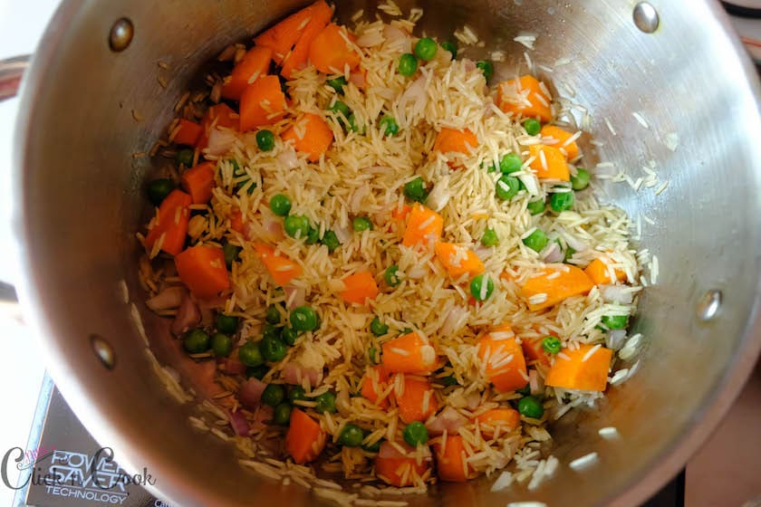 Long grain rice, peas,carrot is being saute in oil in a deep cooking pan