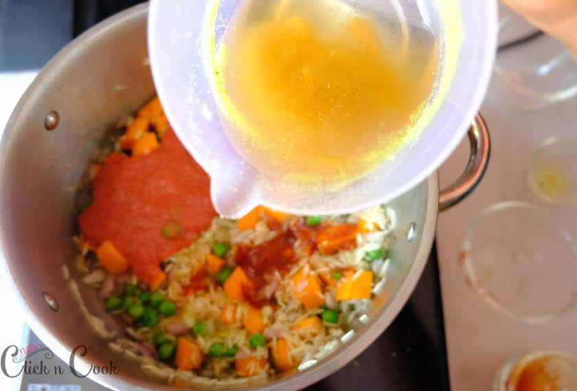 Vegetable stock is being poured in tomato mixture,long grain rice, carrot, peas cooked in deep sauce pan