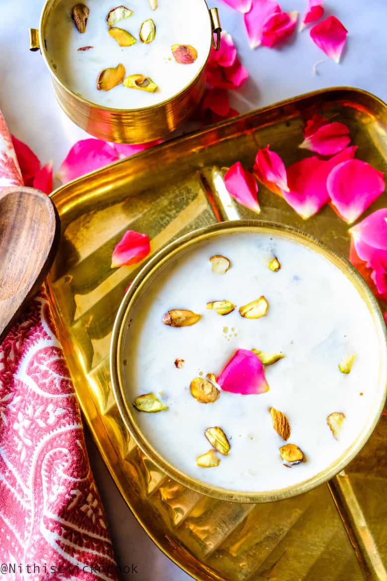 Tender coconut kheer is displayed in brass bowl served over the plate with wooden spoon aside