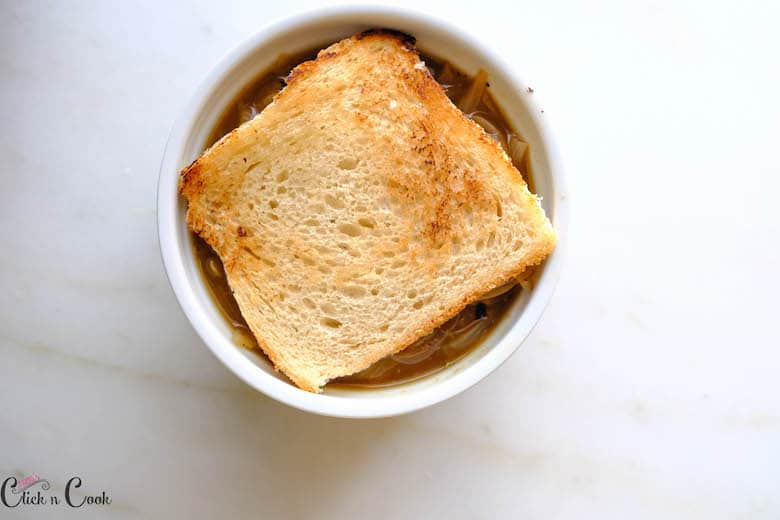 toasted bread is placed over the french onion soup in ramekin