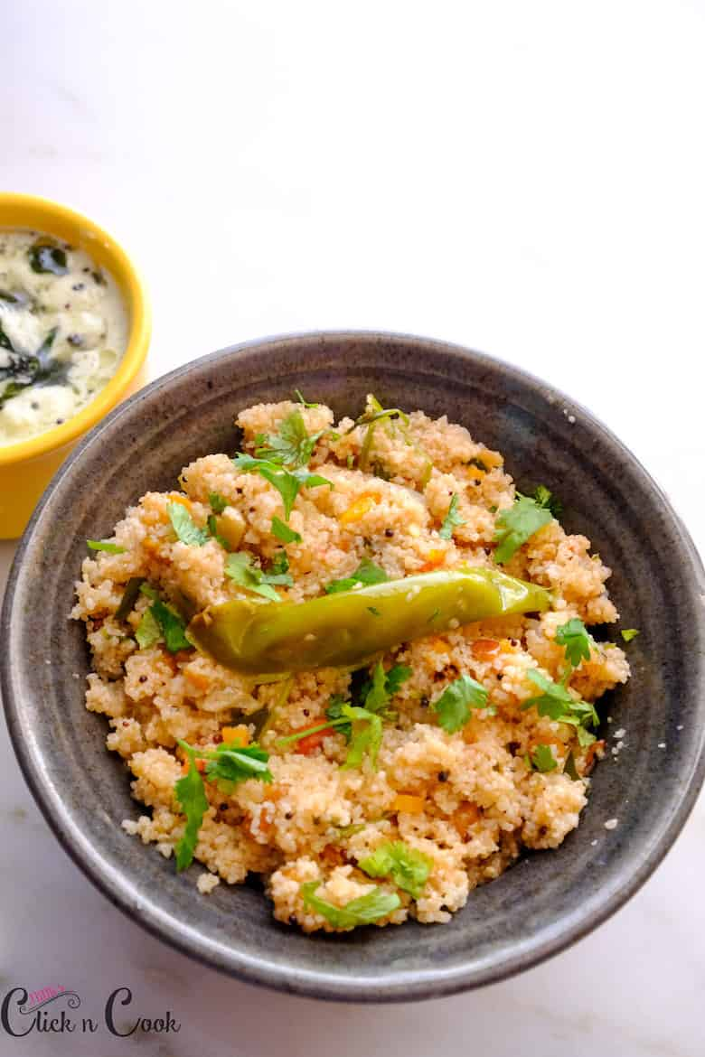 Broken wheat upma is served in black bowl with coconut chutney aside
