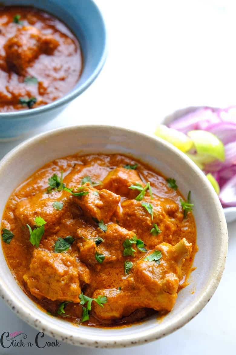 a bowl of indian butter chicken sprinkled with coriender leaves with onion and lemon aside