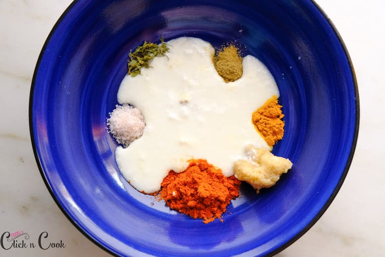 yoghurt is being added to spices in blue mixing bowl