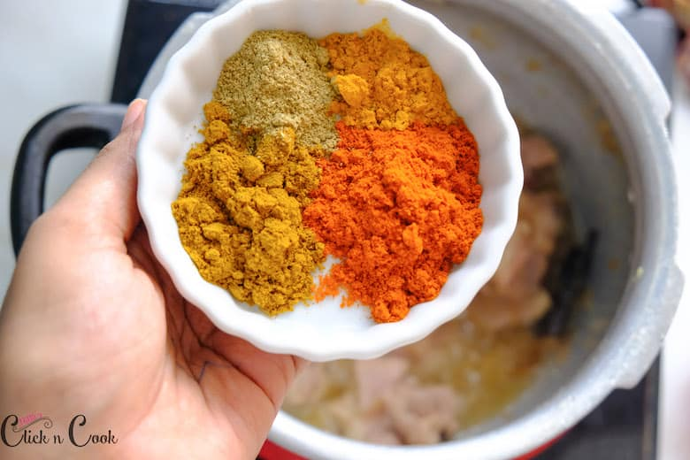 A bowl of spice powders are being added to the deep pot