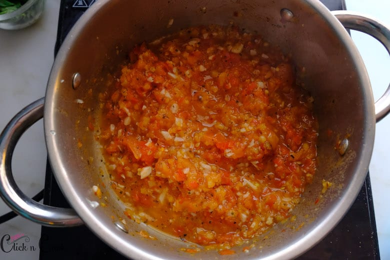 marinara sauce is being cooked in deep sauce pan