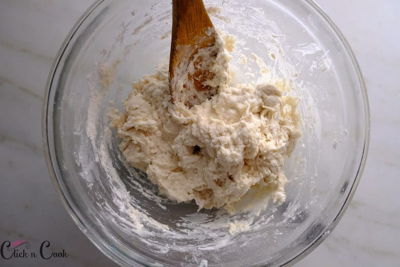 Dough is being stirred in mixing bowl using wooden ladle