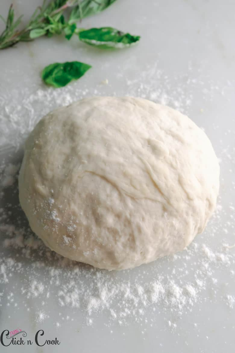 Freshly made homemade pizza dough rolled to make round ball shape dusted with flour