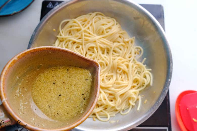 bowl of egg sauce is being added to pasta cooking in saute pan