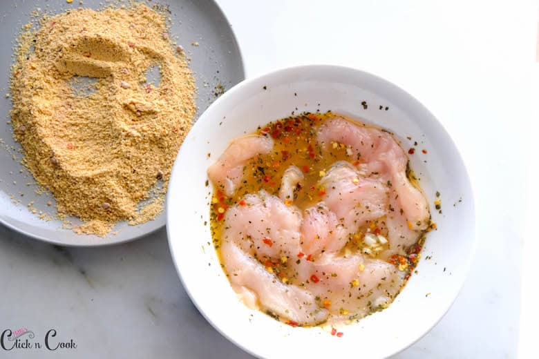 chicken breast marinade in white bowl and bread crumbs in grey plate are taken