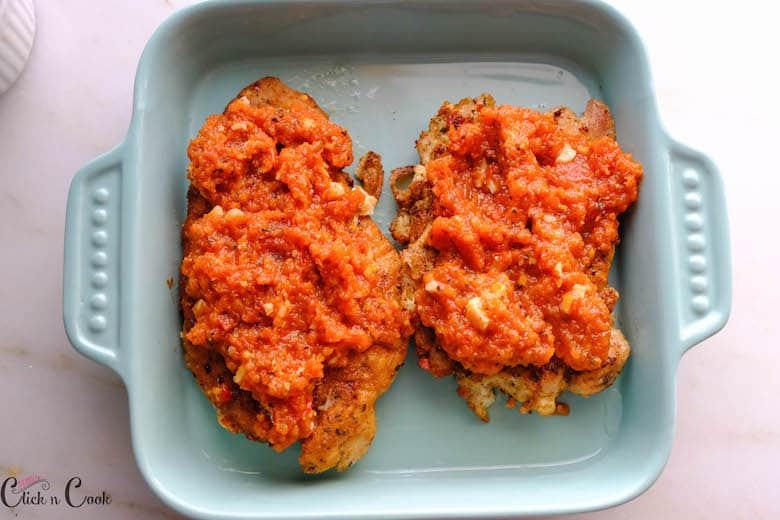 mariana sauce is placed over the fried chicken breast kept over the blue baking dish