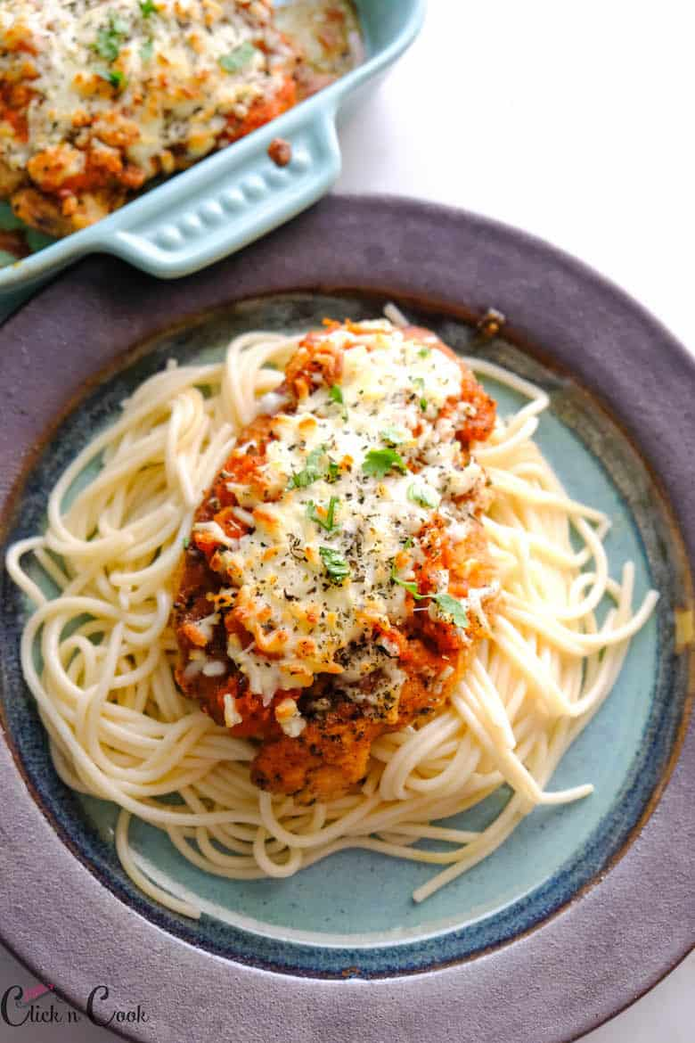 chicken parmesan served over the sphagetti with baking dish aside