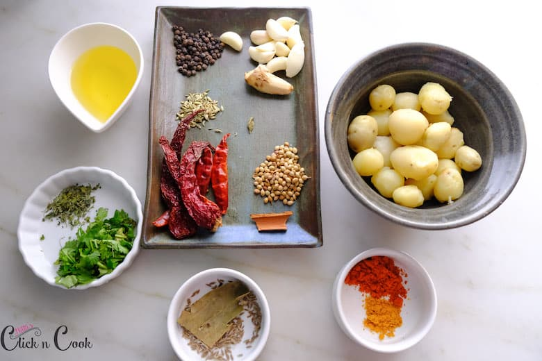 ingredients to make dum aloo is taken in plates and bowls