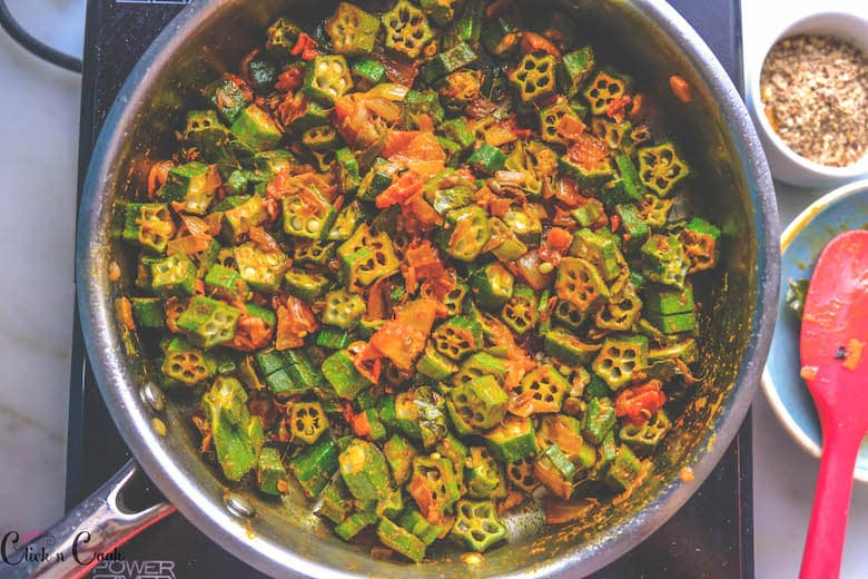okra is being cooked with tomato masala in saute pan