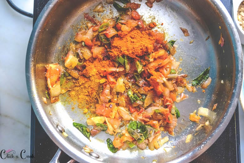 spice powders are added in saute pan along with chopped onions