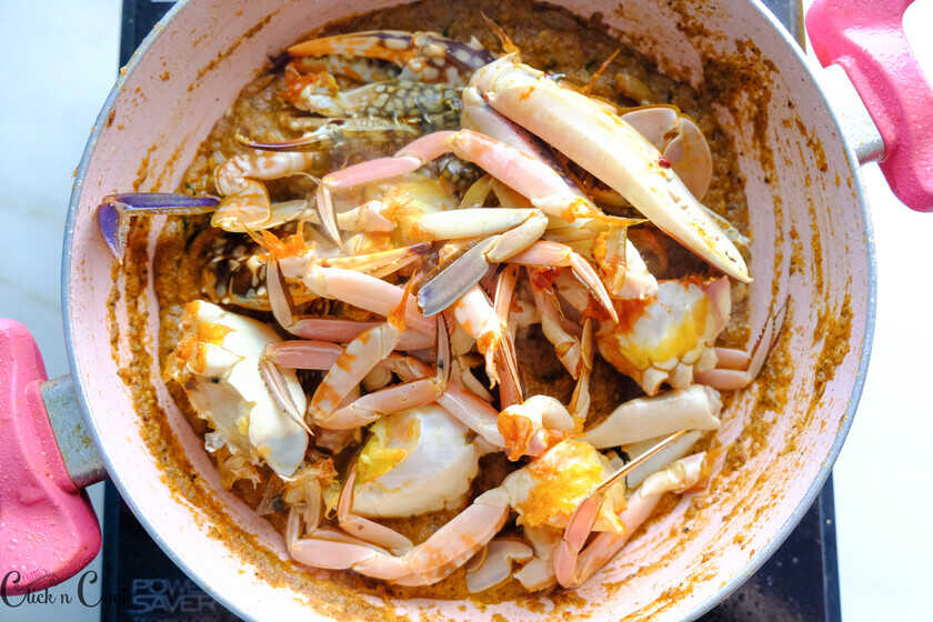 crabs are being added to the gravy in a pan