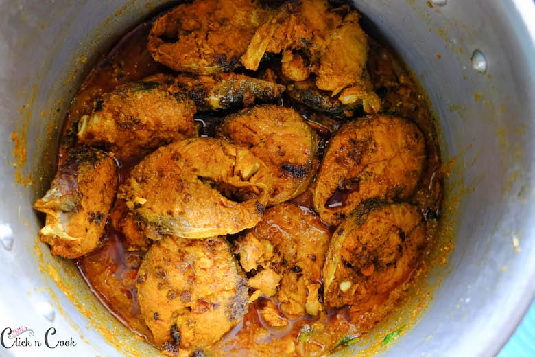 fried fish is being added to masala in deep pot
