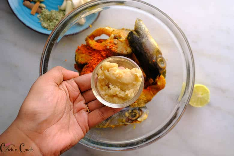 a small bowl of ginger garlic paste is being added to fish in glass bowl