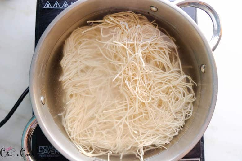 noodles are being boiled in water in deep pot