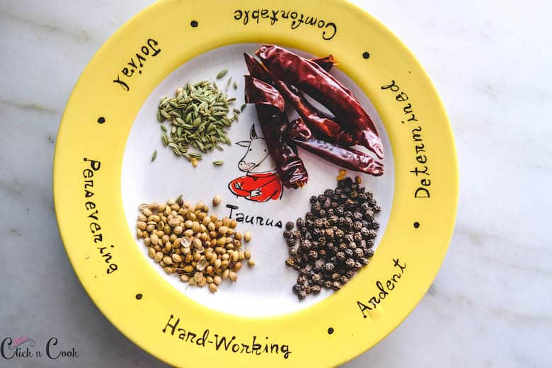 fennel seeds, dry redchilles, coriander seeds, pepper corns are taken in plate