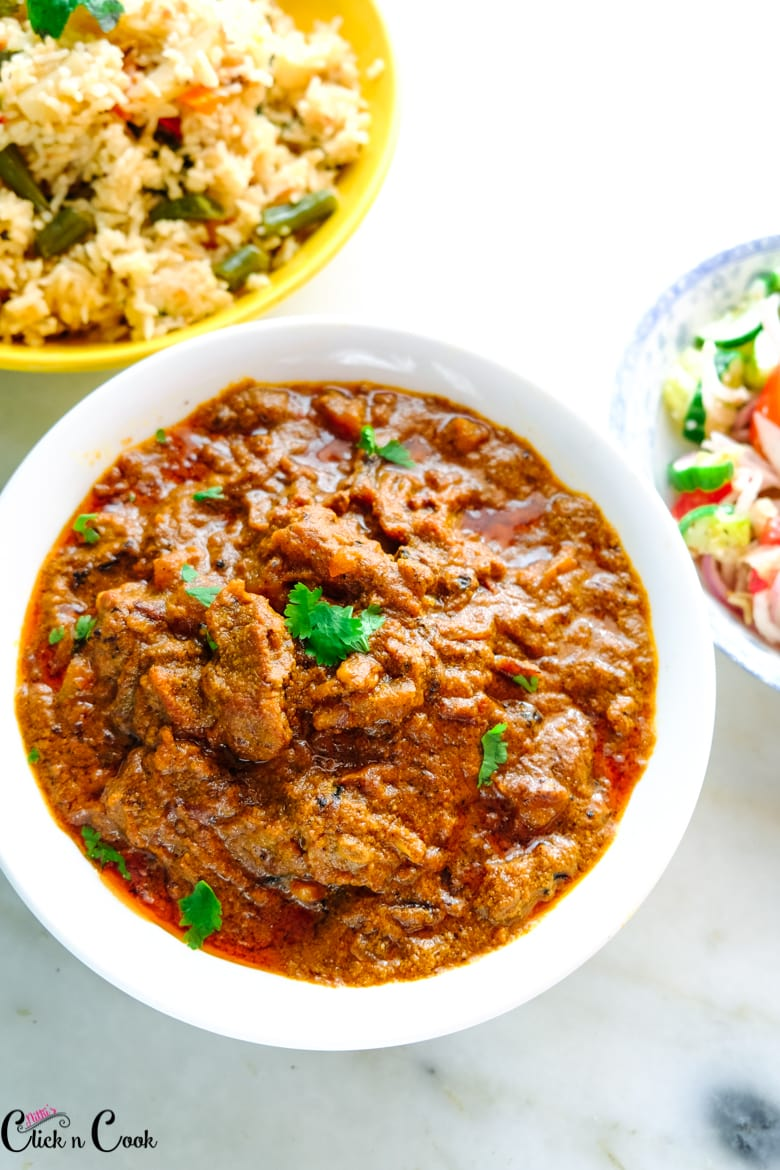 spicy mutton curry served in white bowl with bowl of rice aside