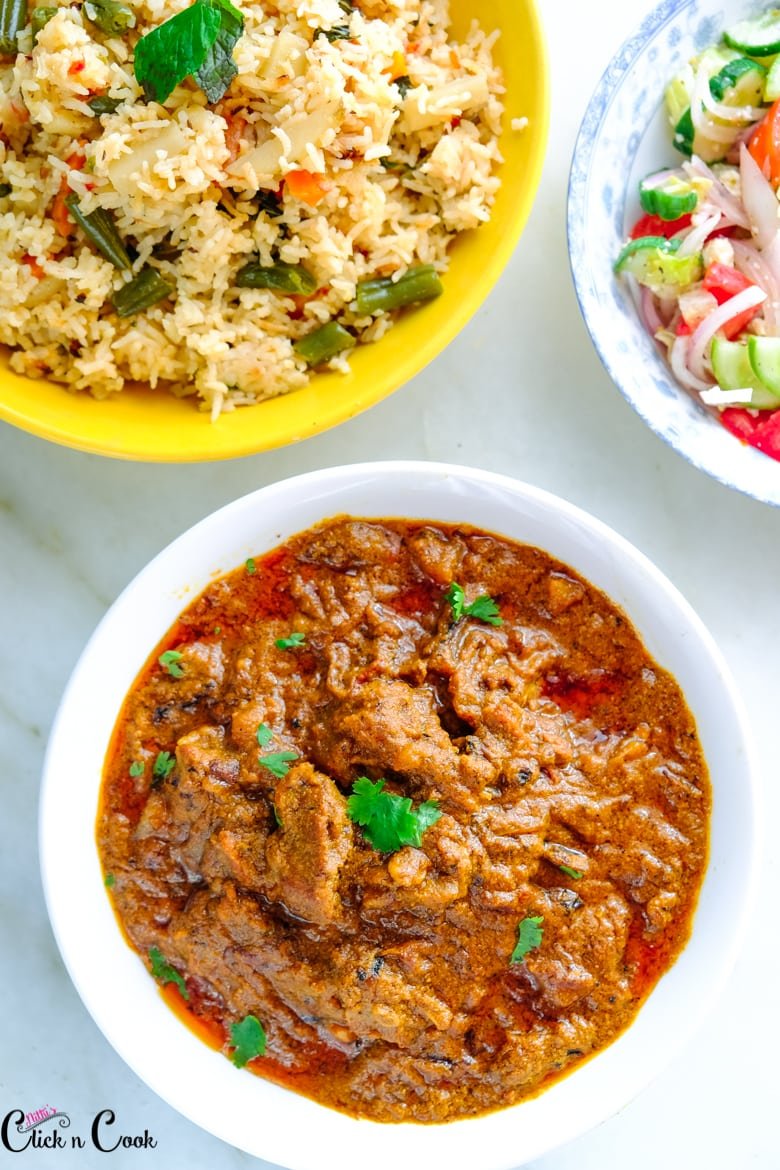 Mutton Kulambu is served in white bowl with bowl of rice aside