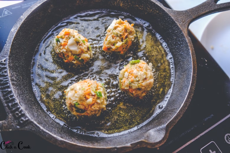 manchurian balls being cooked in cast iron pan