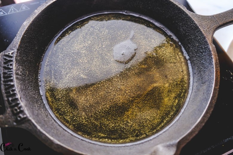 oil is being heated up in cast iron pan