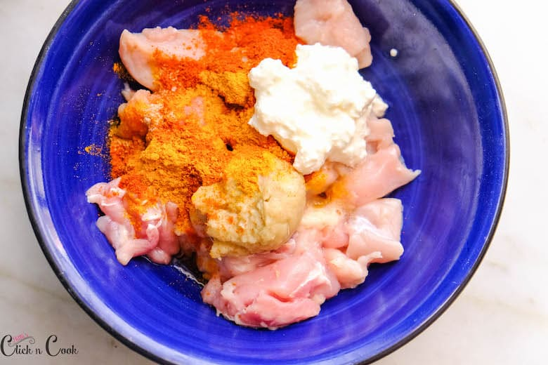 yoghurt and spices are being added to chicken in bowl