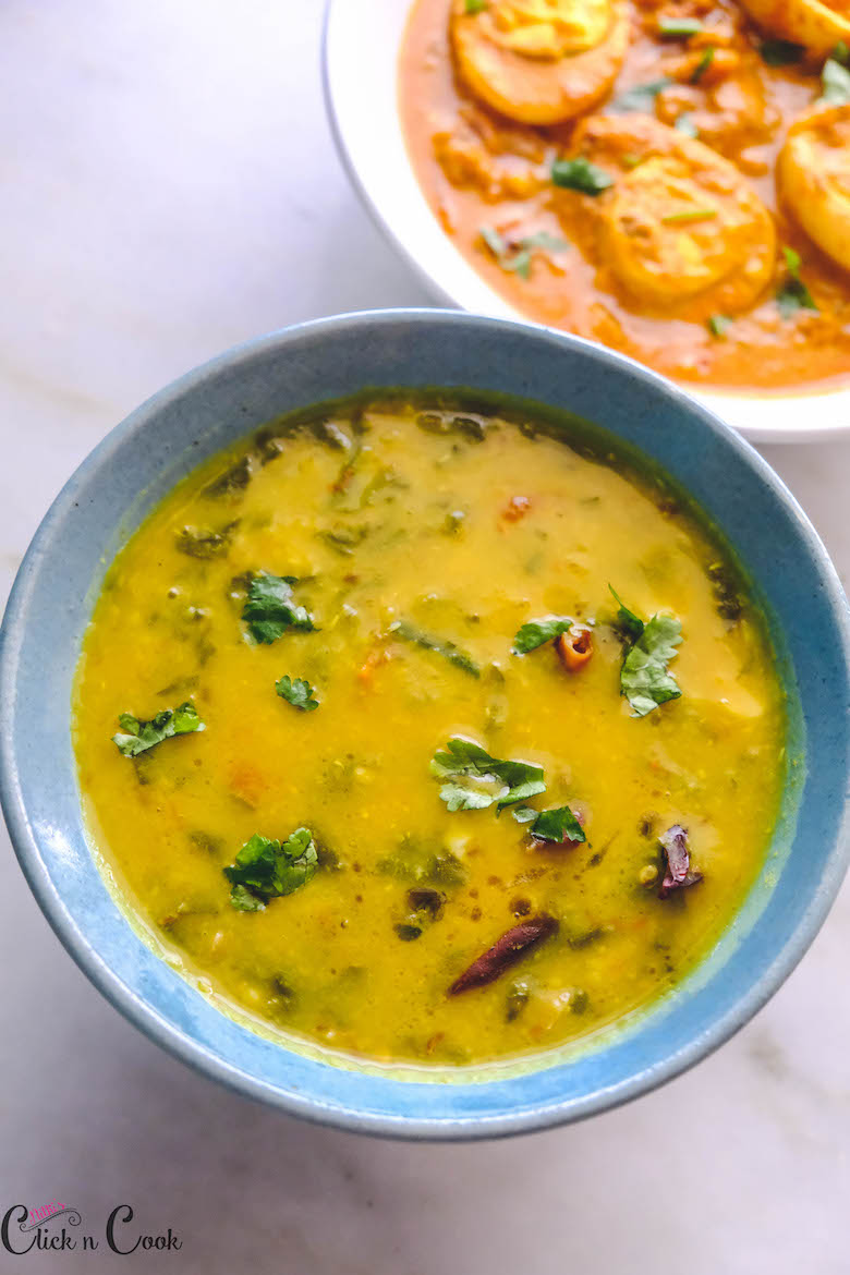 Dal Palak served in blue bowl with egg curry aside