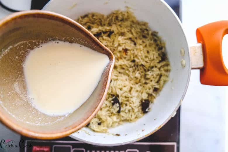 bowl of milk is being added to rice in deep pot