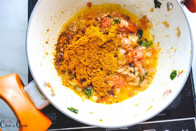 chilli powder and turmeric powder is being added to deep saute pan