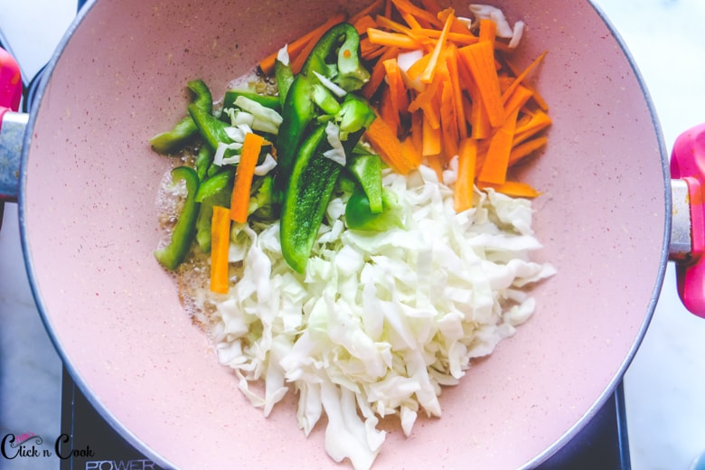 veggies like carrot, cabbage and capsicum are taken in sauce pan