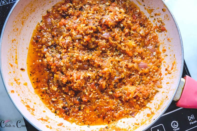 pasta with red sauce is being cooked in saute pan